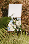wedding rings in a wooden box filled with flowers on the green grass and fern