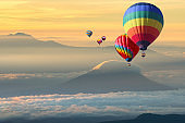 Cappadocia at sunrise - landscape with hot air balloons flying over mountain valley in sunlight  travel concept background, romantic holiday or ballooning festival.