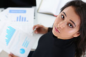portrait of young brunette businesswoman study documents in office