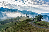 Beautiful mountain landscape of a foggy morning with and old house, trees and clouds