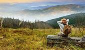 Woman traveler with backpack enjoying sunset on peak of mountain.
