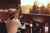 Young woman traveler sits at the terrace with a tablet.