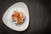 Top view of vegan salad made of carrots and radish decorated with truffle