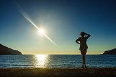 Tourist woman on sea shore enjoying sunset