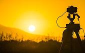 Camera taking picture film of sunrise