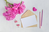 Mockup white greeting card and envelope with pink peonies