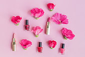 Flat lay pattern with pink flowers and female cosmetics