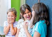 Carefree girls looking at friend in school