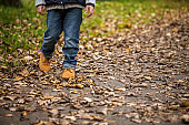 Low section of boy walking in park during autumn