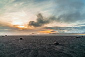 Black sand on dramatic landscape during sunset