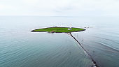 Small green island with rocky pathway and lighthouse.