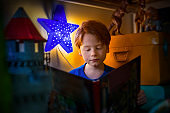 Close-up of boy reading book by illuminated star
