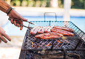 Cropped image of man barbecuing meat for friends in garden.