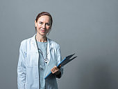 Portrait of doctor with clipboard against wall