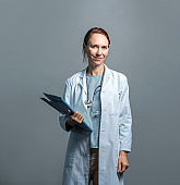 Portrait of confident mature doctor against wall