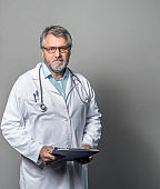 Portrait of senior doctor with clipboard