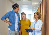 Doctor showing reports to man and pregnant woman