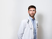 Male doctor day dreaming with hands behind back