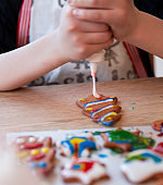Boy decorating Christmas tree cookie with icing