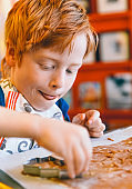 Red hair boy with cutter making gingerbread biscuits