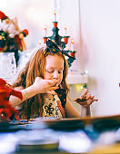 Girl making while tasting cookie in Christmas