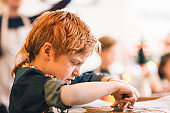 Boy with cutter making gingerbread biscuits