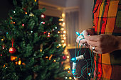 Man with lights decorating Christmas tree at home