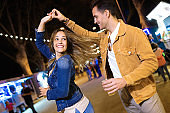 Carefree young couple dancing holding hands in eat market in the street at night.