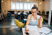 Hipster girl works in creative office or cafe. Young woman holding a cup while looking at some paper.