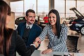 Smiling woman buying car at showroom. Car saleswoman and customer handshake.