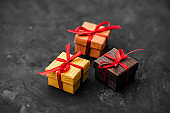 Three small gift boxes on dark background.