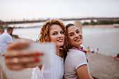 Close-up image of two female friends making selfie outdoors.