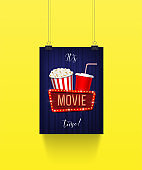 Vector poster hanging on paper clips with pop corn basket, cola cup and movie sign on blue curtain background. It's movie time banner template.