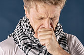Man with cold and flu illness suffering from a headache and cough. Blue background