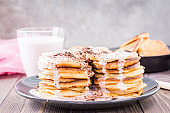 A pile of pancakes stuffed with fruit yoghurt and sprinkled with grated chocolate on a plate