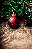 Christmas tree branches with red ball decoration on wooden background. Copy space. Nature New Year Holiday concept