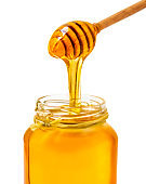Wooden dipper with dripping honey and glass jar isolated on white background, macro