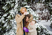 Young Caucasian boy with a beard and a girl have a date outdoors in the winter park against the background of a snowy conifer tree play snowballs, throw snow, hang themselves and play winter games