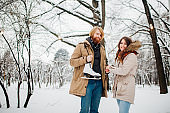Winter and date. Young couple, lovers man and woman in winter on a background of snow and forest holding hands and smiling. A guy with long hair and a beard is holding skates and looking at the girl