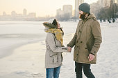 Theme Christmas holidays winter new year. Young stylish Caucasian loving couple Heteresexual walking on the shore of a frozen lake. Date. Valentines Day in winter at sunset. Love and Romance Theme