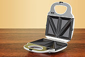Opened sandwich maker on the wooden table. 3D rendering