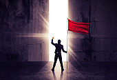 Businessman standing  and holding red flag. Concept for success.