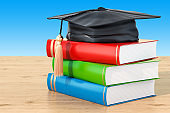 Education concept with books and graduation cap on the wooden table, 3D rendering