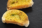 Crunchy garlic bread on dark background