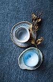 Blue toned ceramic dishware on indigo cloth. Flat lay.  Hand crafted ceramic. Copy space