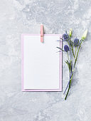 An arrangement of flowers and blank paper cards on gray background