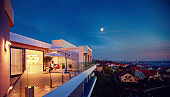 family relaxing on roof top patio with evening city view