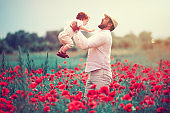happy family, father with infant baby boy playing in poppy flower field at summer day