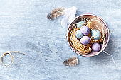 Speckled Easter Eggs and Feathers in a Ceramic Bowl (flat lay arrangement)