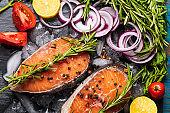 salmon fish on ice, on black board with onion, rosemary, salt, tomato, spices, lemon.